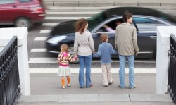 mother and father holds hand of children and standing near road