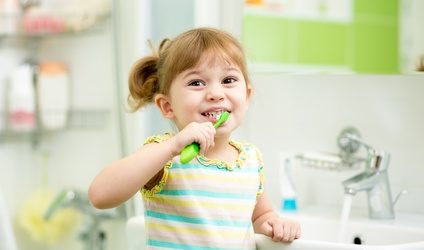 kid girl brushing teeth in bathroom