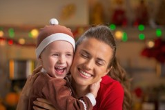 Portrait of happy mother and baby hugging in christmas decorated kitchen