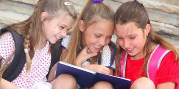 happy schoolgirls with a book outdoors