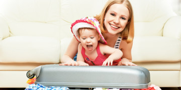 Mother and baby girl with suitcase baggage and clothes ready for traveling on vacation