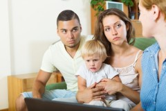 unhappy parents and baby  sitting in front of social worker