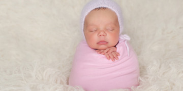 A sleeping nine day old newborn baby girl bundled up in a pink swaddle. She is propped up on a cream colored flokati (sheepskin) rug and wearing a knitted angora bonnet.
