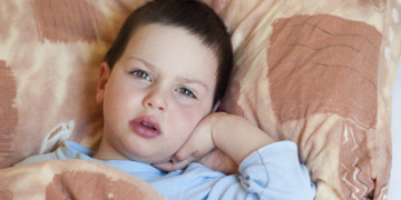 Ill or sick tired child boy sleeping in bed.