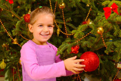 Adorable toddler girl holding decorative toy ball on Christmas tree branch