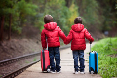 Two boys on a railway station, waiting for the train with suitcases