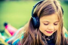 Girl with Headphones Listen Music While Relaxing in the Park.