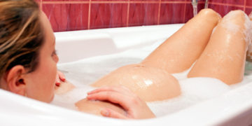Young pregnant woman taking a bath