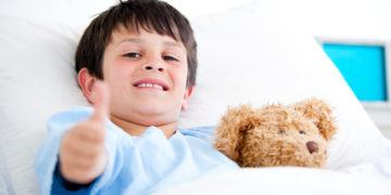 Little boy with thumb up hugging a teddy bear lying in a hospital bed