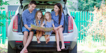 Family with kids looking at map while travel by car