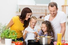 23386779 - happy young family with mum, dad and two young children cooking in the kitchen preparing a spaghetti meal together