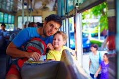 father and son traveling in public bus through asian city