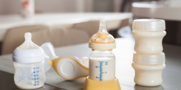 Baby bottle with milk and manual breast pump. A lot of full bottles with breast milk on the background. Mother's milk - the most healthy food for newborn