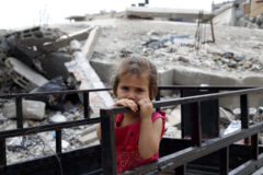 On 24 June, a young girl holds a railing outside her family's partially destroyed home, in the Shejaiya neighbourhood of Gaza City. She is among some 60 children and 20 adults from the same family living in the house, which was hit during an air strike a year ago. The rubble and debris from the dwelling – visible behind her – serves as the children's playground.  In late June 2015 in the State of Palestine, children and families are still struggling to recover from the violence that engulfed Gaza for over seven weeks during July and August 2014. The conflict killed 539 children and injured 2,956, leaving many struggling with life-long disabilities. More than 108,000 people, half of them children, were left homeless. Many continue to live amid ruins. Over 12,600 housing units were completely destroyed but rebuilding has yet to begin, prolonging hardship for some 100,000 people, half of whom are children. As a result of the conflict, more than 308,000 children also remain in need of psychosocial support. UNICEF has appealed for over US $37.3 million to meet the humanitarian needs of children in the State of Palestine during 2015, of which $27.4 million will help affected children and caregivers in Gaza recover from last year's crisis.